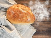 Still life with bread on the background of the tablecloth and old wood. Scattered on the table flour. Composition in a Royalty Free Stock Images