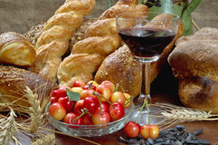 Still life with bread, cherry, and wine on wooden table. Stock Photos