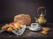 Still life with bread. Italian ciabatta, French croissants in a straw plate with cloth napkin, Vintage copper teapot, white tea cup and saucer with silver royalty free stock image