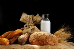 Still life with bread and milk, lit by the sun.  Stock Images