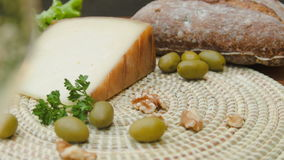 Still life of bread, olives and nuts, tomme cheese stock video
