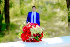 Still life with Bridal bouquet close-up and groom. In the background, the symbol of the wedding day Stock Photography