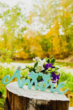 Still life of a bride bouquet, wedding rings and carved wood word Royalty Free Stock Image