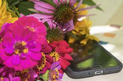Still life with bright summer garden flowers and a mobile phone. Shallow depth of field stock photo