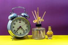 Still life with broken alarm clock, empty essential oil, classic Stock Photo