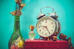 Still life with broken alarm clock, old glass vase with dead ros Royalty Free Stock Photo