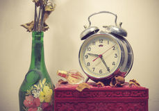 Still life with broken alarm clock, old glass vase with dead ros Royalty Free Stock Photos