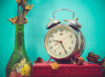 Still life with broken alarm clock, old glass vase with dead ros Stock Photos