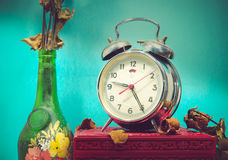 Still life with broken alarm clock, old glass vase with dead ros Royalty Free Stock Image