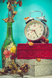 Still life with broken alarm clock, old glass vase with dead ros Stock Photo