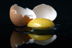 Still-life with a broken egg. On black background with reflection stock image
