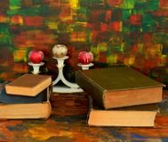 Still life - bronze candlestick and old books.Old wooden table. The old library royalty free stock photo