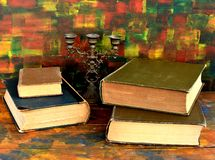 Still life - bronze candlestick and old books.Old wooden table. The old library royalty free stock images