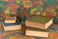 Still life - bronze candlestick and old books.Old wooden table. The old library stock photos