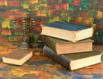 Still life - bronze candlestick and old books.Old wooden table. The old library stock image