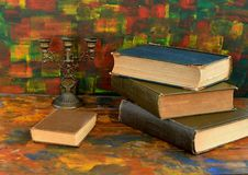 Still life - bronze candlestick and old books.Old wooden table. The old library stock photo