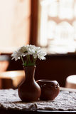 Still life. A brown clay vase with chrysanthemum stands on a table with a white tablecloth in the restaurant hall Royalty Free Stock Photos