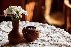 Still life. A brown clay vase with chrysanthemum stands on a table with a white tablecloth in the restaurant hall Royalty Free Stock Images