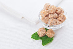 Still life with brown lump sugar, on white linen Royalty Free Stock Photo