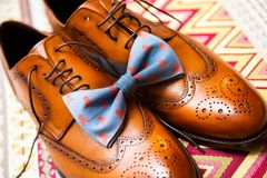 Men`s shoes and a blue bow tie with printed skulls stock photography