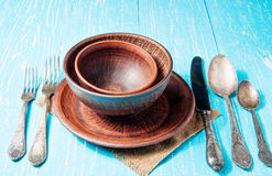 Still life with brown rustic ceramic plate and old cutlery set Royalty Free Stock Image