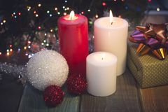 Still life with burning candles, Christmas-tree decorations and a gift box stock photos