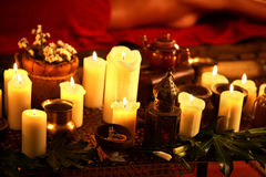 Still life with burning candles and massage herbs. Royalty Free Stock Photography