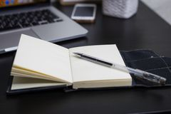 Still life, business, office supplies or education concept : Top view image of open notebook with blank pages and laptope and pen royalty free stock photos