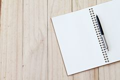 Top view image of open notebook with blank pages and pen on wooden background with copy space royalty free stock image