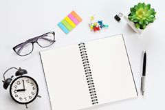 Working desk with open notebook, eyeglasses and alarm clock Stock Images