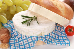 Still life with Camembert cheese. Round creamy soft camembert cheese with grapes, baguette and nuts royalty free stock image