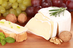 Still life with Camembert cheese. Round creamy soft camembert cheese, cut on slices with grapes and walnuts stock images