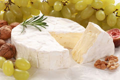 Still life with Camembert cheese. Round creamy soft camembert cheese, with a wedge cut out with grapes and walnuts royalty free stock image