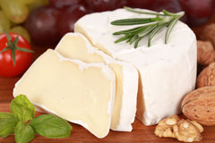 Still life with Camembert cheese cut on slices. Round creamy soft camembert cheese, cut on slices with grapes and walnuts Royalty Free Stock Photo