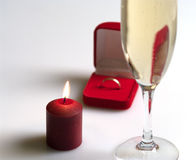 Still life with a candle and champagne. Small box with a gold ring, tall wine glass of champagne and conflagrant candle. Focus on a candle Royalty Free Stock Photo