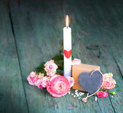 Still life with a candle for mothers day. On an old shabby wooden table Stock Images