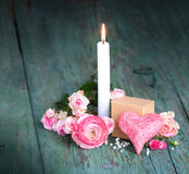 Still life with a candle for mothers day. Still life in pink with a candle for mothers day on an old shabby wooden table Stock Photo