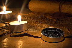 Still life with candles by a compass and old maps Royalty Free Stock Images