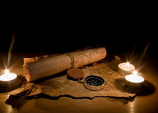 Still life with candles by a compass and old maps Stock Photo