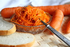 Still life: carrot salad with white loaf. Carrot salad with white loaf on a rice laying Royalty Free Stock Photography