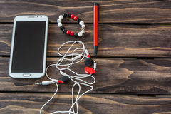 Still life with cell phone,headset,pen and bracelet Royalty Free Stock Photo