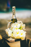 Still life of champagne tropical flowers stemware and bridal rings. Still life of the bottle of champagne white tropical flowers glass stemware and bridal rings stock photo
