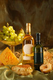 Still life with cheese, bread, grapes and two bott Royalty Free Stock Image