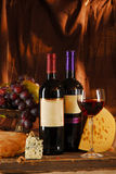Still life with cheese, bread, grapes and two bott Royalty Free Stock Images
