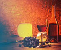 Still-life with cheese, grapes and glass of red wine. Still-life with cheese, grapes and glass and bottle of red wine.Filtered image: vintage effect Stock Photo