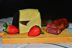 Still life with cheese, loin and strawberries. Taprrom with cheese, loin and strawberries Royalty Free Stock Images
