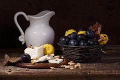 Still life with cheese, quince , plums and white pitcher Royalty Free Stock Images