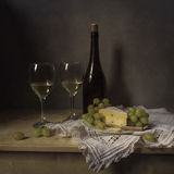 Still Life Cheese, wine, grapes. With a dark bottle closed cork, poured two glasses with wine and cheese with mold, grozddyami grapes on vintage plate standing stock photo