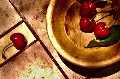 Still life of cherries in nature into wood bowl and over stone table stock photo