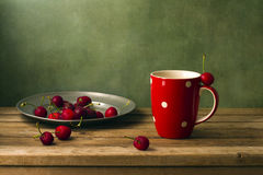 Still life with cherries and red cup Royalty Free Stock Images